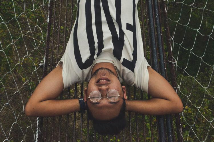 Directly above shot of young man sleeping on footbridge