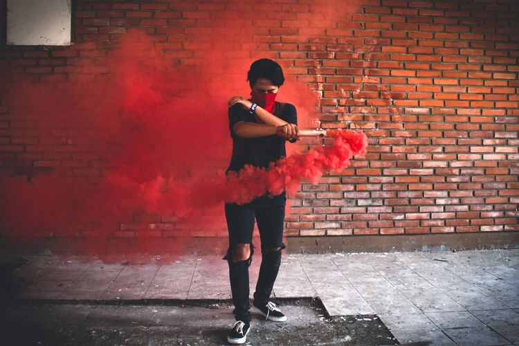 Full length of man holding distress flare while standing against brick wall
