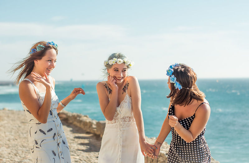 Happy friends standing by bride against sea