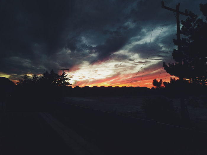 Scenic view of silhouette landscape against dramatic sky during sunset
