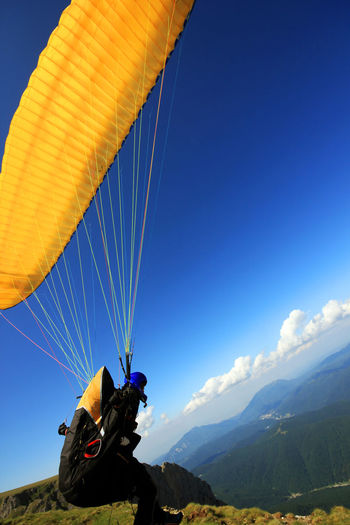 Paraglider with parachute on mountain against blue sky