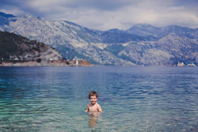 Portrait of cute boy swimming in river against mountains