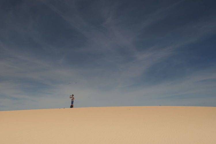 Man Standing In Desert Against Sky