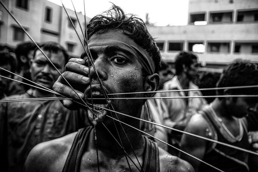 The Eye of Faith - A staunch devotee with several metal piercings through his mouth during a Hindu festival of Gajan or Charak, which is celebrated mainly in the last two days of the month of Chaitra (around mid April) in rural Bengal to appease Lord Shiva. The festival is associated with devotees painting their bodies, playing with fire, undergoing body piercings etc. to signify a form of penance. Mastering their fears is the key to undergoing such an extreme ritual. Such inner faith makes me wonder and get inspired. Debarshi Mukherjee Photography Documentary Photography Faith God India Inner Power Photojournalism Ritual Traditions West Bengal Close-up Culture Debarshimukherjee Extreme Rituals Festival Human Face People Portrait EyeEmNewHere Focus On The Story The Portraitist - 2018 EyeEm Awards Be Brave This Is Strength