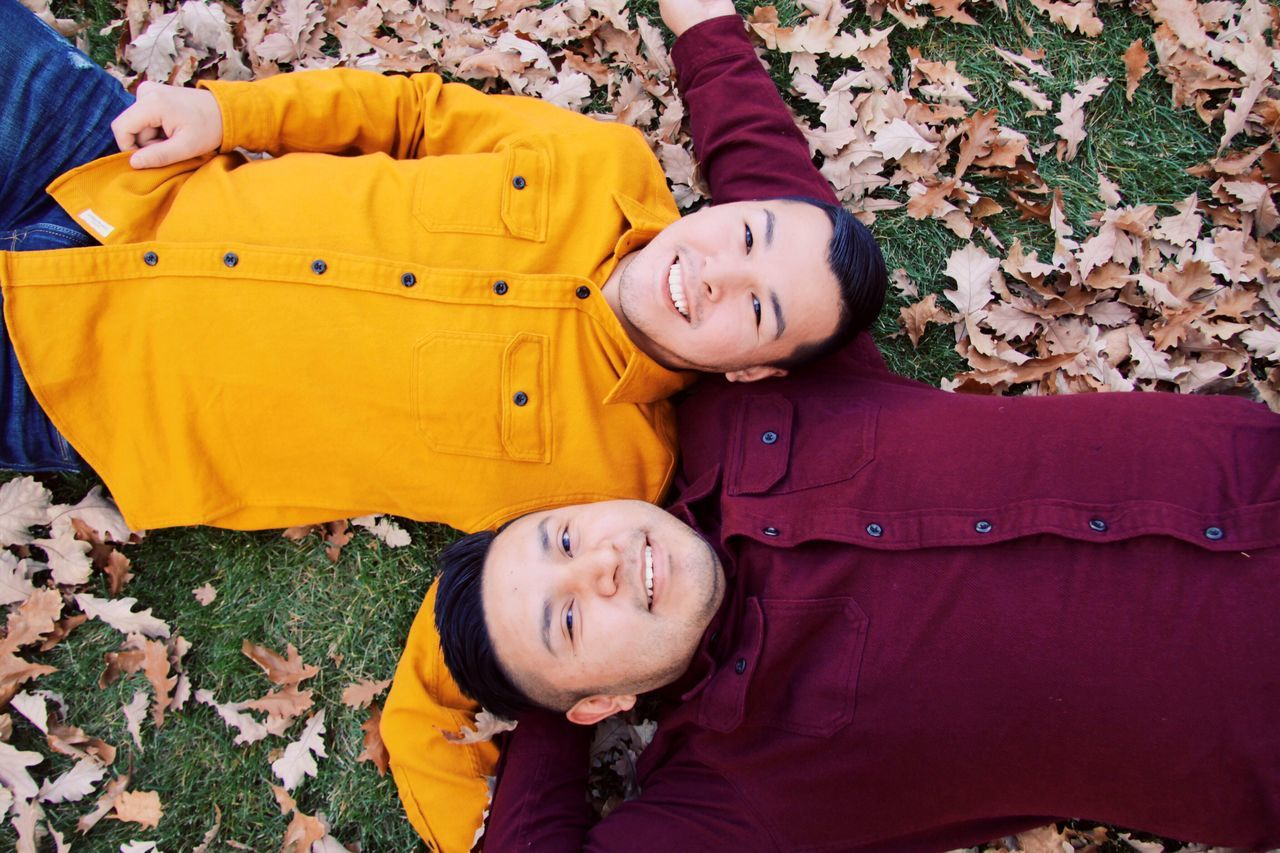 Portrait Of Smiling Young Friends Lying On Leaves Covered Field During Autumn