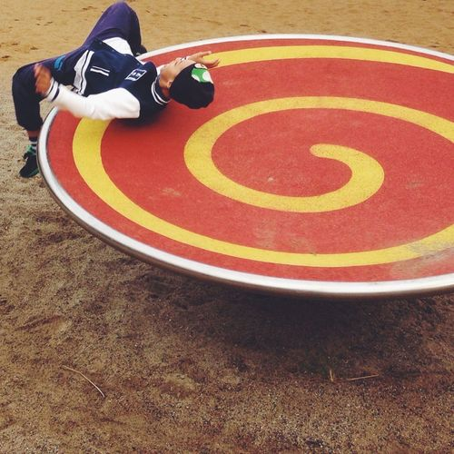 High angle view of boy playing on roundabout at playground