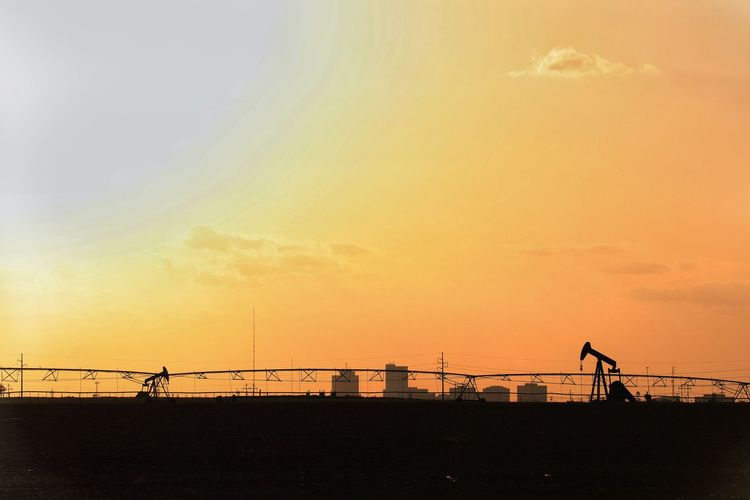 Golden Midland skyline with pump jacks and irrigation system Silhouettes Midland, TX Permian Basin Golden Agriculture Petroleum Industry Texas Landscape Texas Energy Fossil Fuel Solar Energy Desert Heat Drought EyeEm Selects Sky Sunset Cloud - Sky Orange Color Silhouette Nature Water Beauty In Nature Scenics - Nature Outdoors Architecture Land Built Structure No People