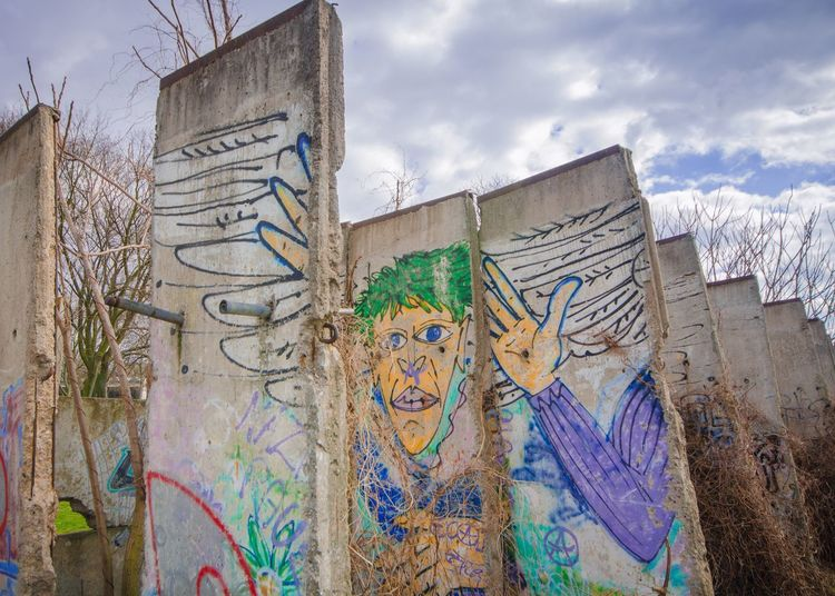 Low angle view of graffiti on berlin wall against cloudy sky