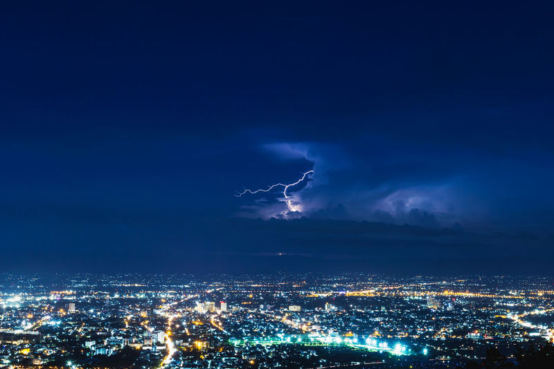 Lightning striking over illuminated cityscape at night