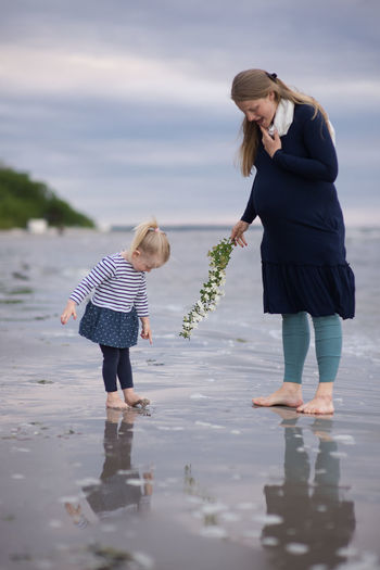 Pregnant woman standing with daughter at beach against sky
