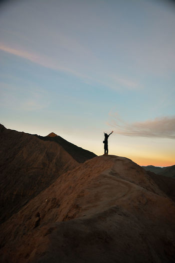 Silhouette man standing on mountain at sunset