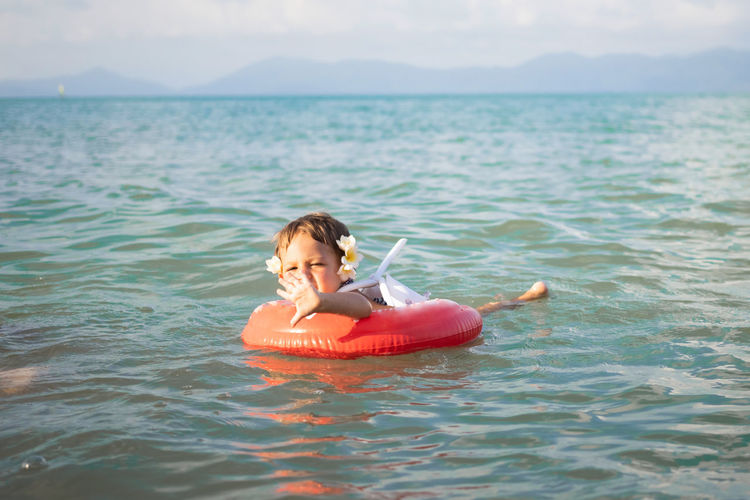 Adorable toddler toddler swim in the sea in a special inflatable life ring.