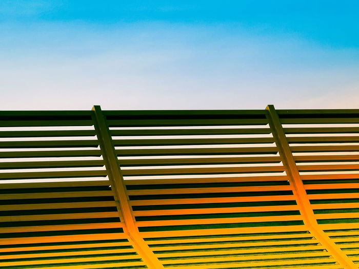 Wooden sun lounger at the beach or on a cruise ship against sunny blue sky.