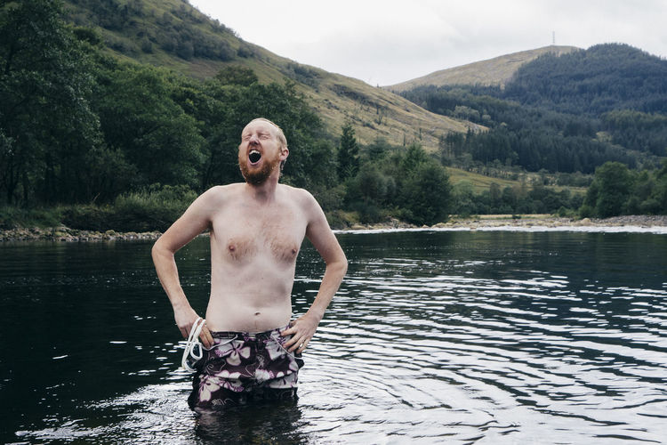 Shirtless man making face while standing in lake