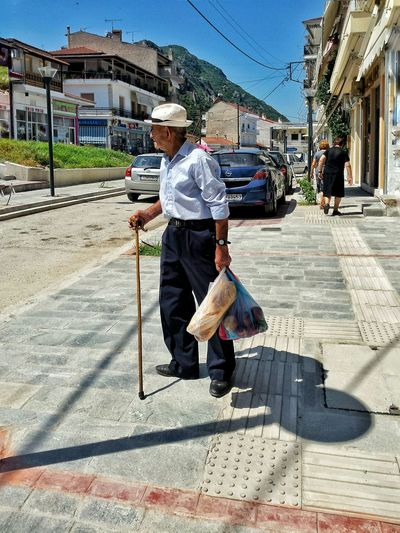 "The Simple Life Sometimes we needed nothing more than a Fresh Bread and Fruit! The Man with Hat and his ""μπαστουνι"" or ""κλουτσιά"" seeing something......... Village Life Streetphotography VisitGreece ........this is more as a little bit Overpimped image! :)"