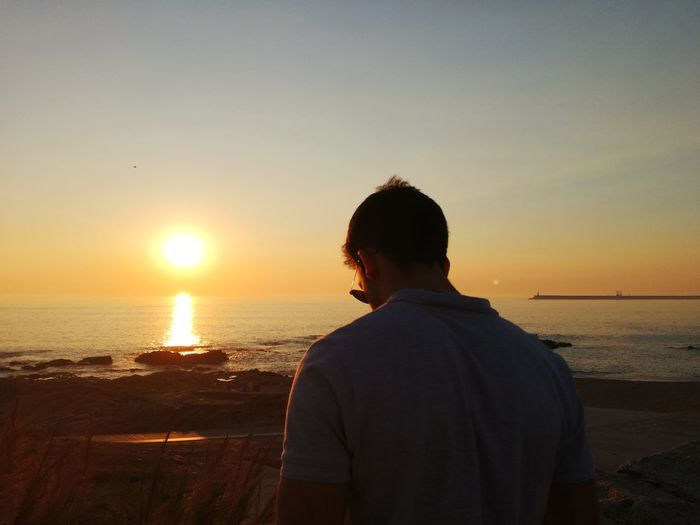 Rear view of man standing at beach during sunset