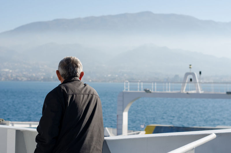 A man is watching the fog while arriving his destination near Patra, Greece. Boat Day Fog Greece Man Mist Mountains One Man Only One Person Outdoors Rear View Sea Sky Transportation Travel Watching Water