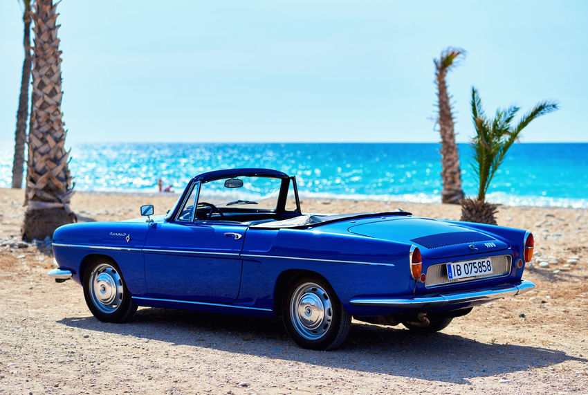 Renault Caravelle or Renault Floride car on the tropical beach. It is a sports car which was produced by the French manufacturer Renault between 1958 and 1968 Automobile Beach Blue Color Cabriolet Car Car Classic Car Convertible Car Editorial  French Idyllic Scenery Outdoors Palm Trees Renault Caravelle Renault Floride Retro Car Sandy Beach Sea Seaside Sixties Summertime Transport Transportation Vehicle Vibrant Color Vintage Car