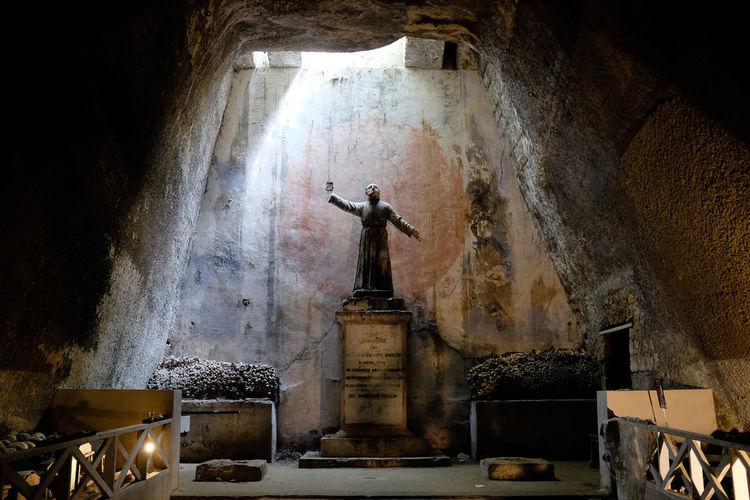 Statue in Fontanelle Underground Cemetery Caves Catacombes Cemetery Naples Statue Altar Architecture Catacombes Day Fontanelle History Human Representation Indoors  Lit From Above Nap No People Priest Sculpture Spooky Statue Tourism