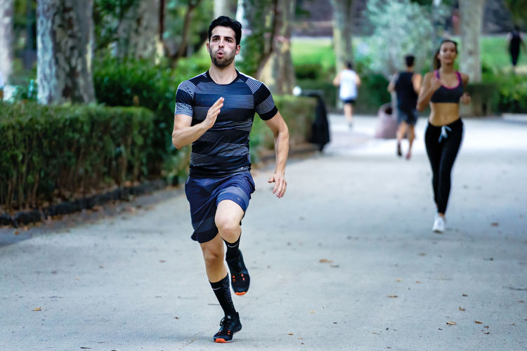 Full length of young man running on footpath