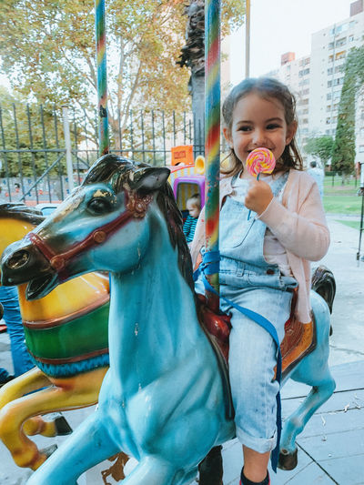 Portrait of a girl with carousel in amusement park