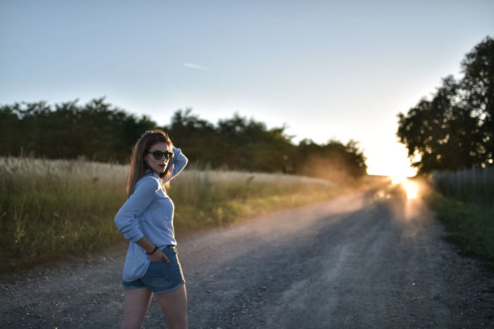 Beautiful Woman Beauty In Nature Country Dust Dusty Road Golden Hour Lifestyle Lifestyles Nature Posing Posing For The Camera Rays Rays Of Light Rear View Road Summer Summer Vibes Sunset Woman Portrait Sommergefühle Connected By Travel Fashion Stories