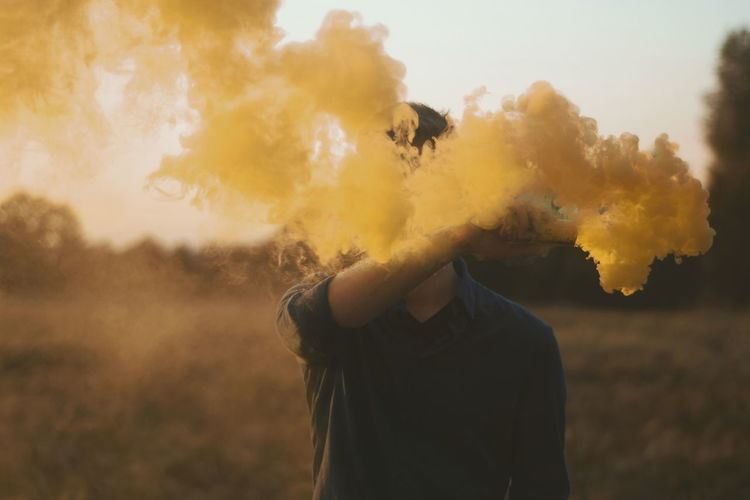 Yellow Smoke Emitting From Distress Flare Being Held By Young Man