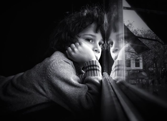 Close-up of thoughtful boy with hand on chin looking through window