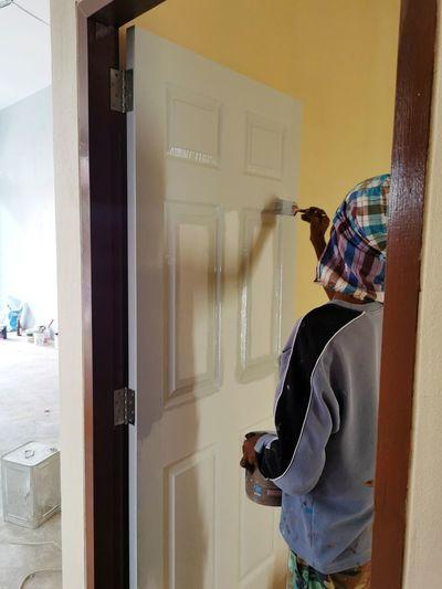Man painting door at home