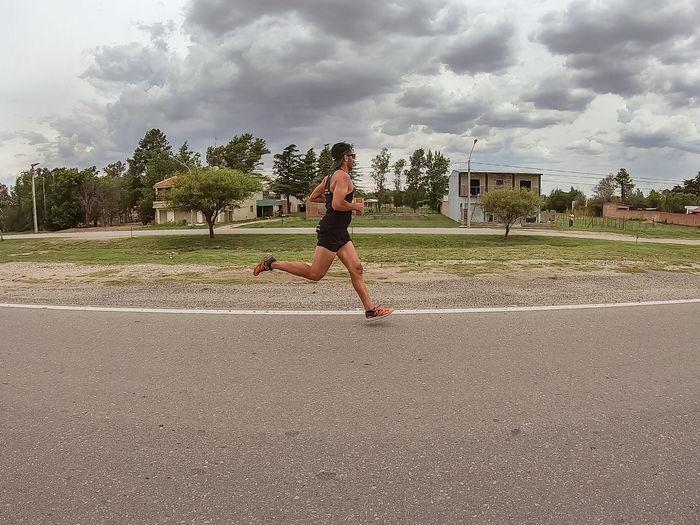 Full length of woman running on road against sky