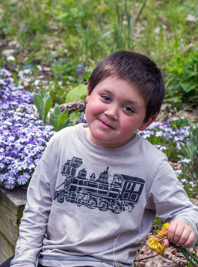 Portrait of smiling boy on purple flowering plants