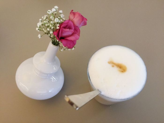 High angle view of latte macchiato by flower vase on table