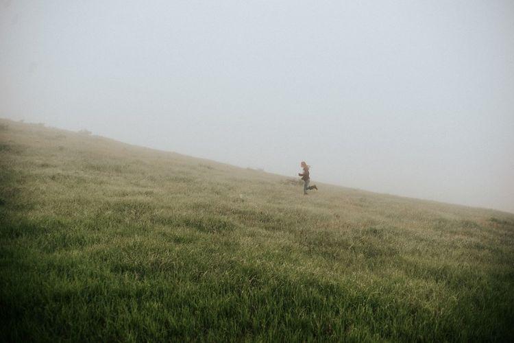 Man on grassy field against sky