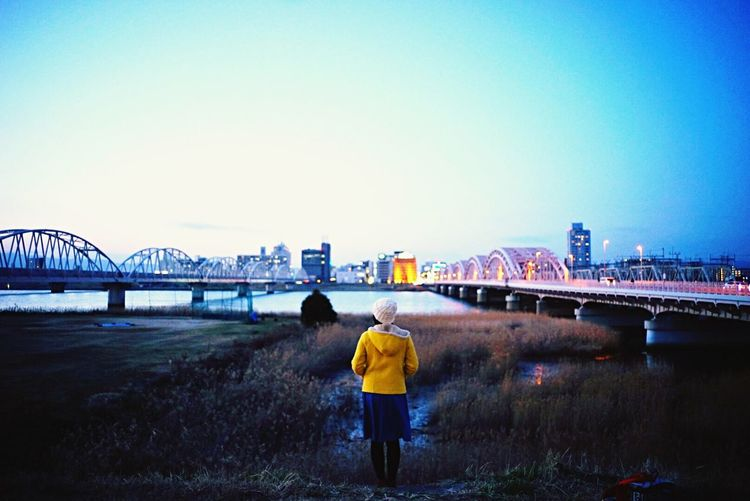 Rear view of woman walking on bridge over river