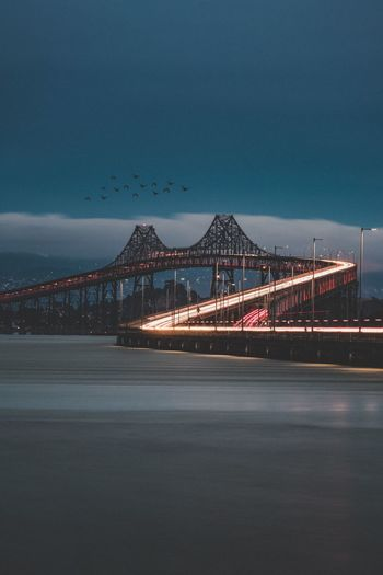 Illuminated bridge over sea against sky in city