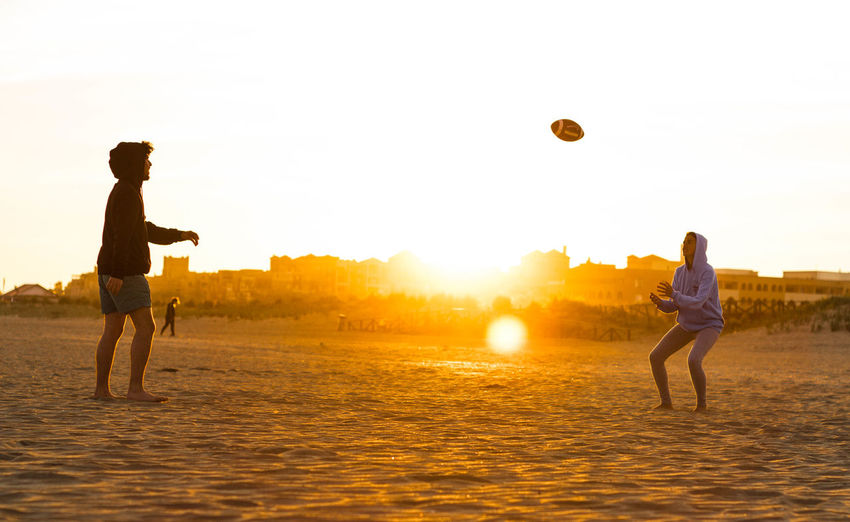 Friends Playing With Rugby Ball At Beach Against Sky During Sunset