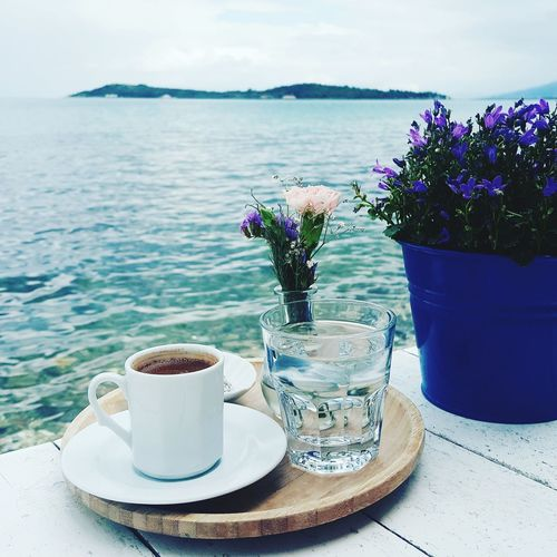 Close-Up Of Turkish Coffee With Vase And Potted Plant By Sea