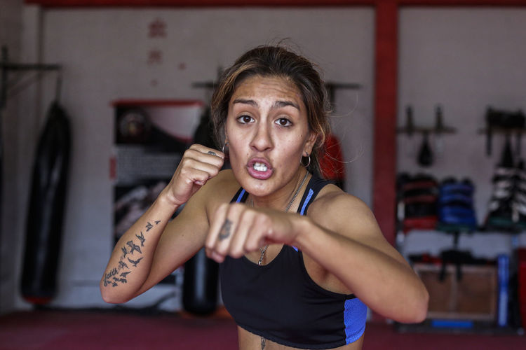 Portrait of woman in fighting stance at gym