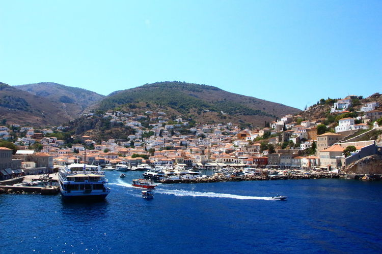 Boats moored in sea by town against clear blue sky