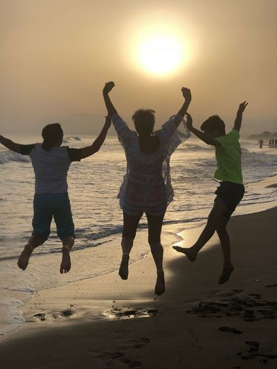 Happy family jumping at beach against sky during sunset