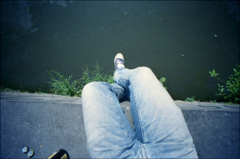 Low Section Of Man Sitting Over Calm Water