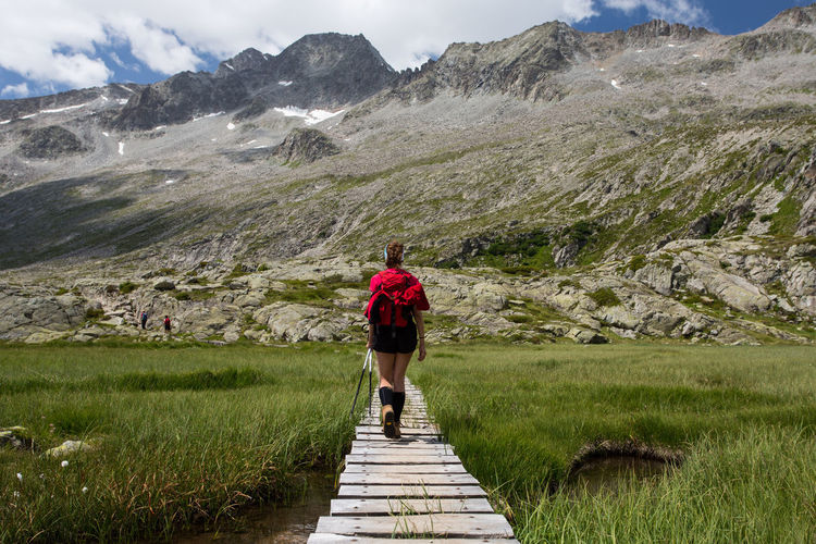 Rear view of woman walking on mountain by lake against mountains