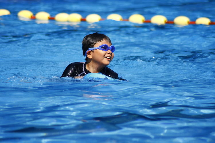 Boy Wearing Goggles Swimming In Pool