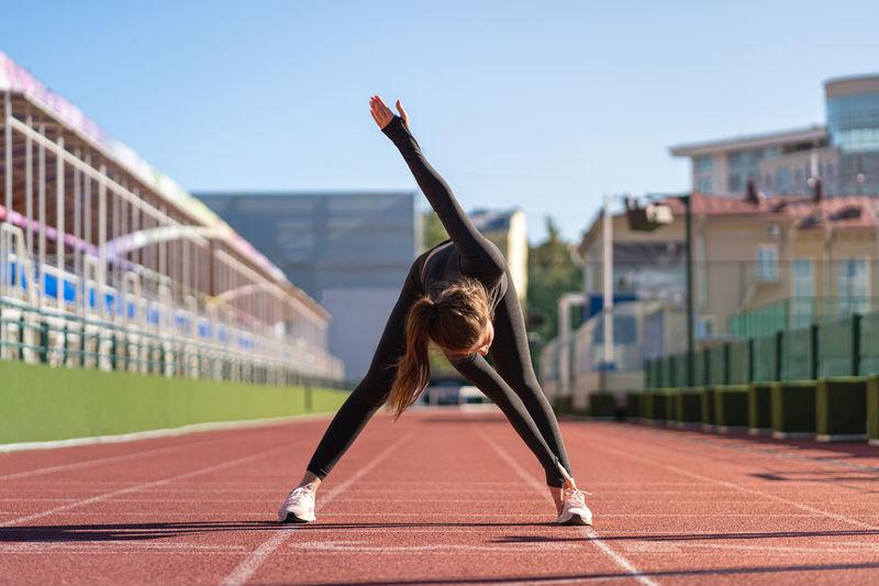 Full length of woman exercising on running track