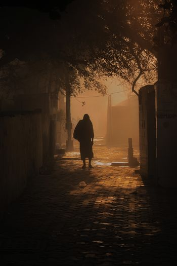 Rear view of silhouette man walking on alley amidst buildings