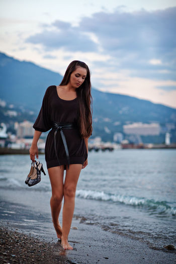 woman walking on beach with shoes barefoot. Girl walking alone near the sea shore. Alone Dreaming Females Lonely Travel Woman barefoot Beach Beauty In Nature Brunette Confused Day High Heels Long Hair Nature Outdoors Sea Shore Summer Sunset Walking Water Young Women