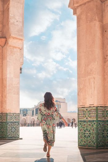 Rear view of woman standing at historical building
