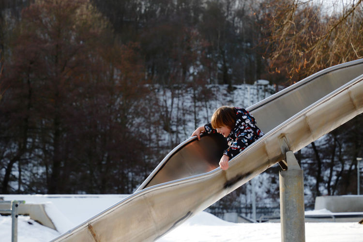 Boy playing on slide over snow covered playground