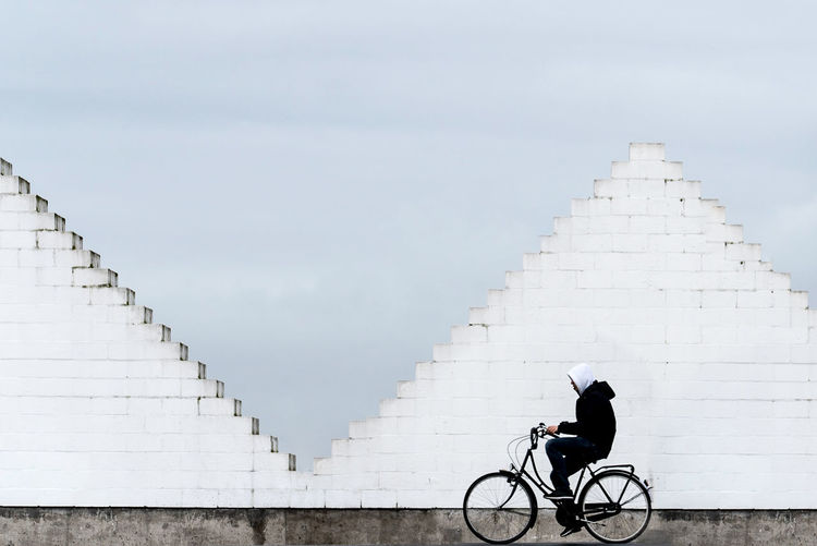 Side View Of Man Riding Bicycle Against Built Structure