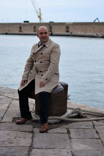 Full Length Of Mature Man Looking Away While Sitting On Pier By River
